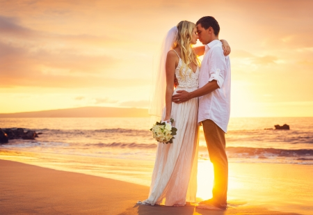 24528611 - bride and groom, kissing at sunset on a beautiful tropical beach, romantic married couple