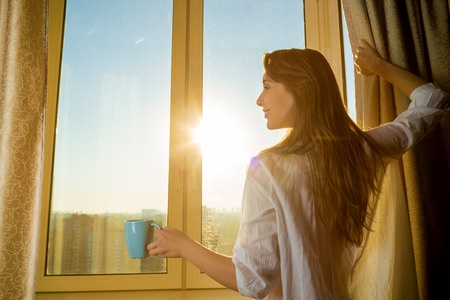 31878158 - woman in the morning. attractive sexy woman with neat body is holding a cup with hot tea or coffee and looking at the sunrise standing near the window in her home and having a perfect cozy morning.