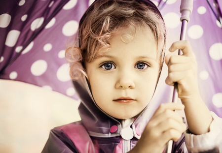 35559234 - little cute girl holding an umbrella, close up portrait