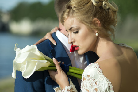 42873580 - lovely young wedding couple of guy in blue jacket embracing blonde woman in white dress with red lips holding bunch of calla flowers standing on sunny outdoor background, horizontal picture