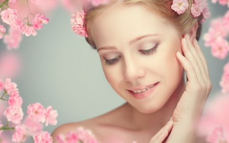 31384290 - beauty face of the young beautiful woman with pink flowers in her hair