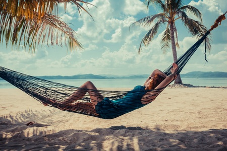 36584318 - a young woman is relaxing in a hammock on a tropical beach