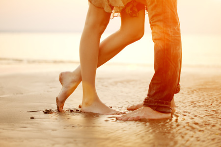 39395526 - a young  loving  couple hugging and kissing on the beach at sunset. two lovers, man and woman barefoot near the water. summer in love