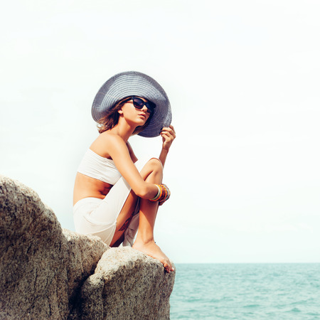 39857693 - outdoor summer sunny fashion portrait of pretty young sensual woman posing in hat and white dress on the rocks and have fun alone on the ocean seashore. outdoors lifestyle portrait
