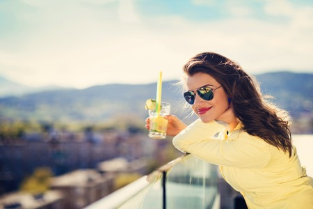 40551953 - attractive young woman with a drink on a terrace of a bar