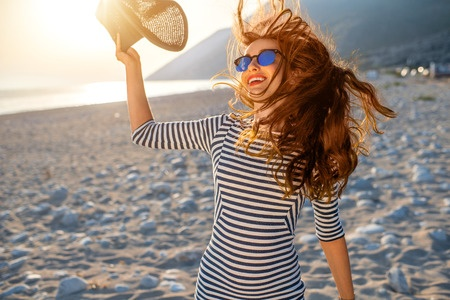 43076305 - young and happy woman in stripped dress jumping with a hat in the hand on the beach on sunset against the sun. feeling free and joyful