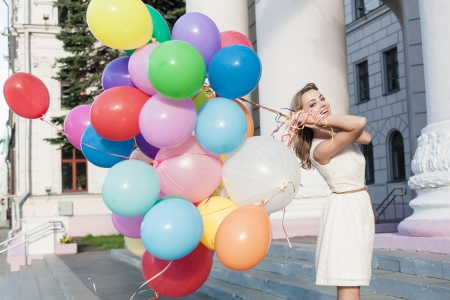 15574973 - happy young woman with colorful latex balloons keeping her dress, urban scene, outdoors