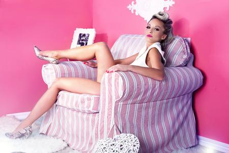 32510679 - luxury beautiful blonde woman posing, sitting in pink room.