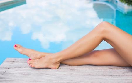 38874745 - beautiful slim women legs by the swimming pool