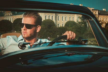 44476048 - confident wealthy young man behind classic convertible steering wheel