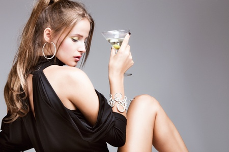 10480417 - young attractive woman with glass of martini, profile, studio shot
