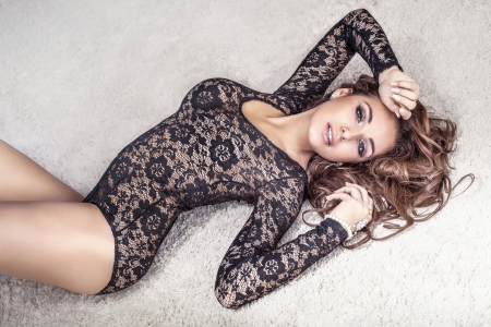 23735889 - sensual brunette woman with long hair lying on carpet in underwear, looking at camera.