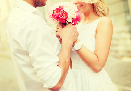 28508118 - summer holidays, love, relationship and dating concept - couple with bouquet of flowers in the city