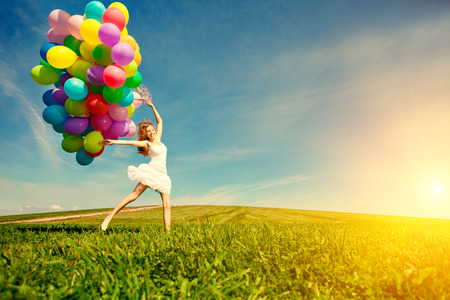 30697231 - happy birthday woman against the sky with rainbow-colored air balloons in hands. sunny and positive energy of nature. young beautiful girl on the grass in the park.