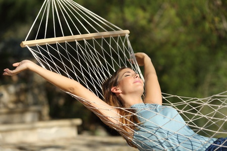 32751873 - happy woman relaxing on a hammock on holidays and raising arms in the mountain