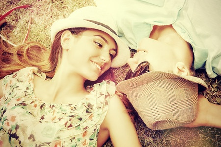 37942362 - happy young couple relaxing on the lawn in a summer park. love concept. vacation.