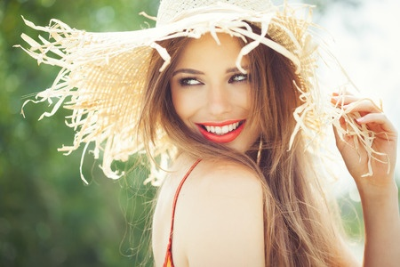 39840318 - young woman in straw hat smiling in summer outdoors.