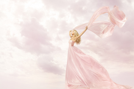41351880 - happy woman in pink long dress, girl with flying silk scarf cloth, joy open arms freedom concept