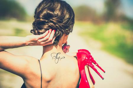 47271183 - barefoot brunette girl outdoor with red high heels in her hands