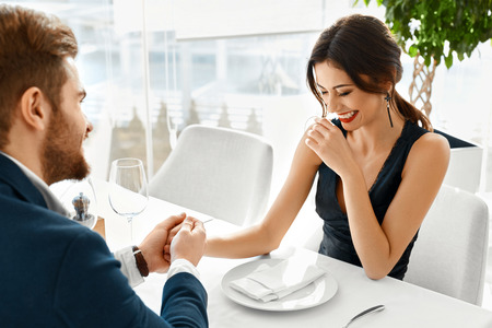 49921173 - couple in love. happy smiling elegant young people celebrating anniversary or valentine's day and having romantic dinner or lunch together in gourmet restaurant. romance, relationships concept.
