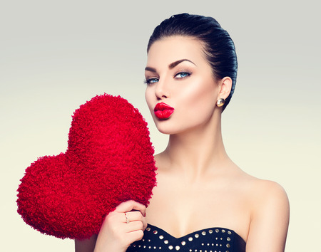 51892359 - gorgeous young brunette woman with heart shaped red pillow