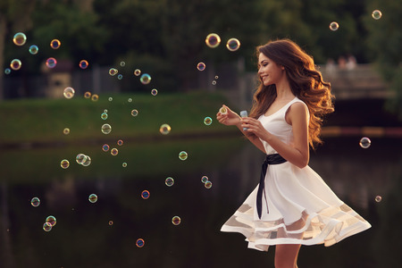 55314554 - outdoor summer portrait of young beautiful happy woman making soap bubbles in park or at nature in white dress
