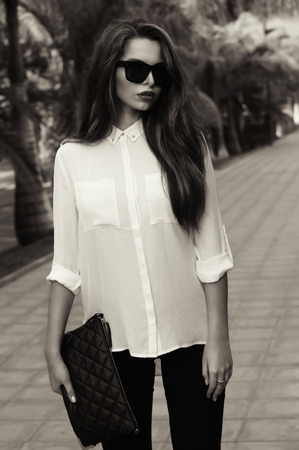 55316350 - young fashionable trendy girl posing at tropical alley between palms in evening soft light. vogue style toned portrait of young woman in black jeans, white blouse and sunglasses holding handbag. monochrome image