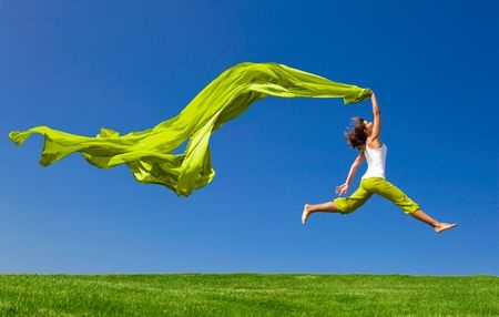 6534247 - beautiful young woman jumping on  a green meadow with a colored tissue