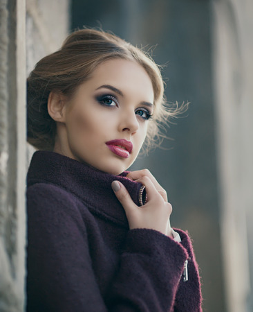 29953668 - beautiful woman with bright makeup wearing a warm jacket in the street