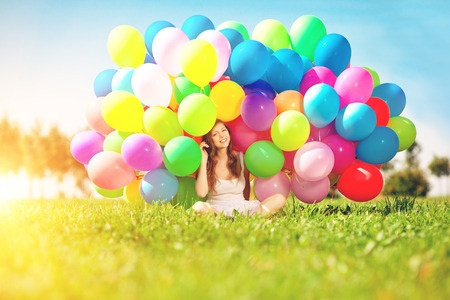 30750674 - happy birthday woman against the sky with rainbow-colored air balloons in her hands. sunny and positive energy of nature. young beautiful girl on the grass in the park.