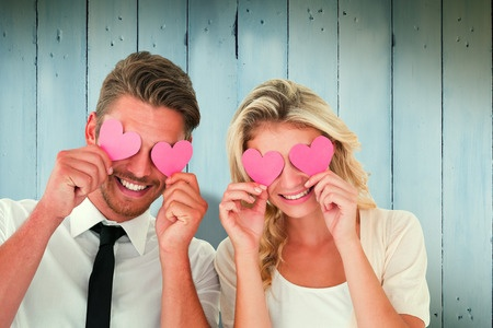 35907007 - attractive young couple holding pink hearts over eyes against wooden planks