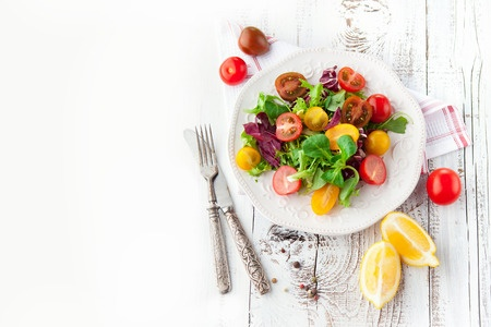 38444478 - fresh salad with cherry tomatoes, spinach, arugula, romaine and lettuce in a plate on white wooden background, top view