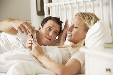 42269920 - husband complaing as wife uses mobile phone in bed