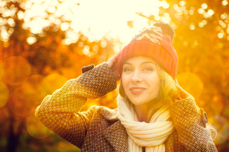 43393739 - young woman in beanie hat on autumn background in sunny day. smiling happy girl portrait. toned photo with bokeh and copy space.