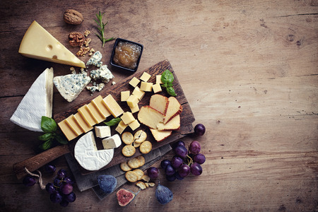 44807393 - cheese plate served with grapes, jam, figs, crackers and nuts on a wooden background