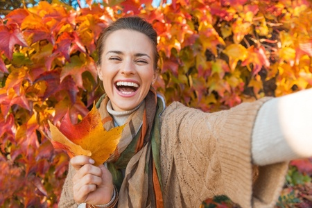 45387366 - portrait of cheerful young woman with autumn leafs in front of foliage making selfie