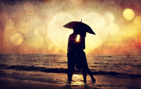 17347546 - couple kissing under umbrella at the beach in sunset. photo in old image style.