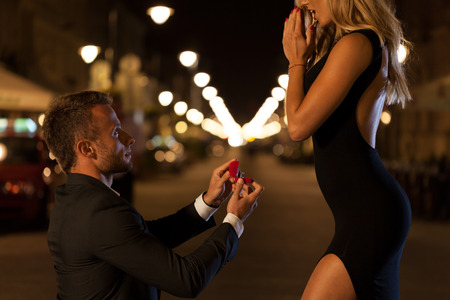33068696 - a man in a suit proposing to his beautiful woman at night