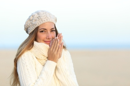 34326659 - woman warmly clothed in a cold winter on the beach with the sky in the background