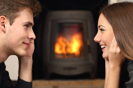 37232672 - side view of a couple flirting and looking each other in front a fireplace