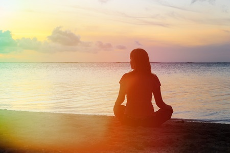 44588740 - young woman meditation on sunset tropical beach