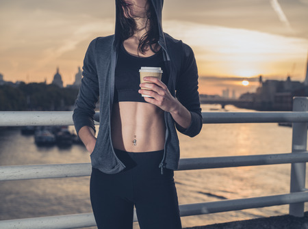 48411884 - an athletic young woman with toned abs is standing on a bridge in london at sunrise with a paper cup in her hand