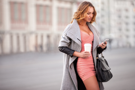 59041241 - a businesswoman checking email via mobile phone and holding a coffee cup against urban scene.