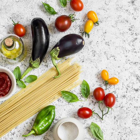 62090655 - raw ingredients for making pasta - spaghetti, eggplant, tomatoes, pepper, olive oil, tomato sauce and basil . cooking background, top view