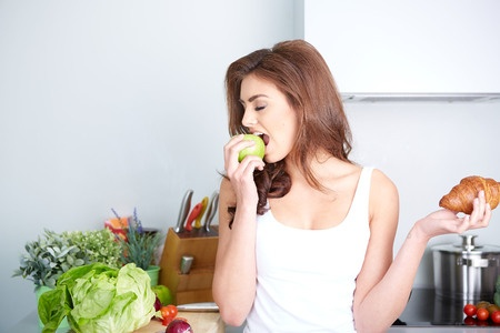 35974568 - diet. dieting concept. healthy food. beautiful young woman choosing between fruits and sweets