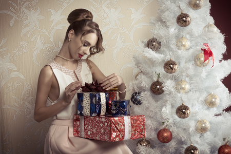 47726886 - elegant beautiful woman with hair-style sitting near decorated tree with some christmas presents. xmas concept.