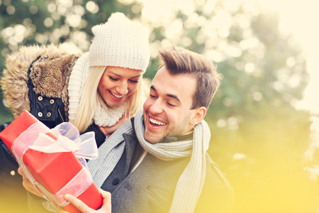 47846763 - a picture of a young couple with a present in the park