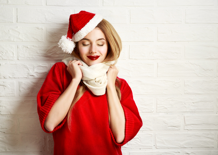 49230538 - smiling christmas girl with closed eyes in red winter clothes at white brick wall background. romantic dreaming woman portrait. toned photo with copy space.