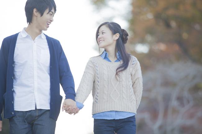 紅葉の中を歩くカップル